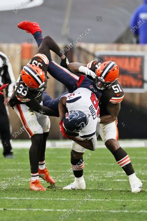 Stock Picture of Cleveland Browns defensive back Ronnie Harrison (33) and linebacker Mack Wilson (51) tackle Houston Texans wide receiver Randall Cobb (18) during the second half of an NFL football game, in Cleveland