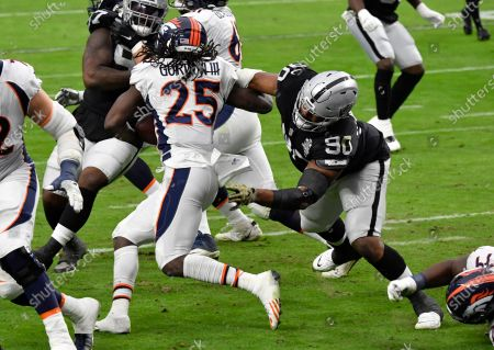 Denver Broncos running back Melvin Gordon #25 is tackled by Las Vegas Raiders defensive tackle Johnathan Hankins #90 during the first quarter of an NFL football game, in Las Vegas