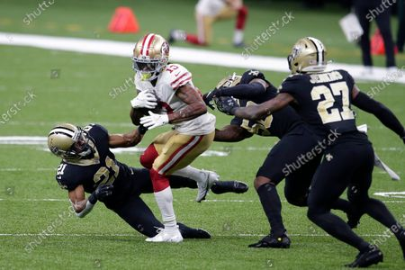 San Francisco 49ers wide receiver Richie James (13) carries against New Orleans Saints cornerback Patrick Robinson (21), outside linebacker Demario Davis and strong safety Malcolm Jenkins (27) in the second half of an NFL football game in New Orleans
