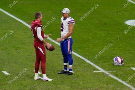 Arizona Cardinals punter Andy Lee speaks with Buffalo Bills punter Corey Bojorquez (9) prior to an NFL football game, in Glendale, Ariz