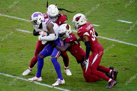 Buffalo Bills wide receiver Stefon Diggs (14) is tackled by Arizona Cardinals cornerback Patrick Peterson (21) and outside linebacker De'Vondre Campbell (59) during the first half of an NFL football game, in Glendale, Ariz