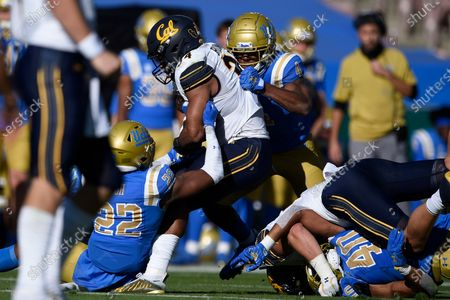 Stock Photo of Defensive back Obi Eboh, left, and Stephan Blaylock, right, stop a run by California running back Christopher Brown Jr. during the first half of an NCAA college football game in Los Angeles