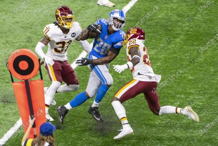 DETROIT, MI - : Detroit Lions RB Adrian Peterson (28) tries to weave through Washington Football Team S Deshazor Everett (22) and Washington Football Team S Kamren Curl (31) during NFL game between Washington Football Team and Detroit Lions on at Ford Field in Detroit, MI