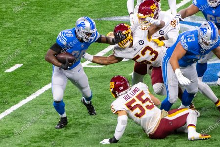 DETROIT, MI - : Detroit Lions RB Adrian Peterson (28) stiff-arms Washington Football Team LB Jon Bostic (53) during NFL game between Washington Football Team and Detroit Lions on at Ford Field in Detroit, MI