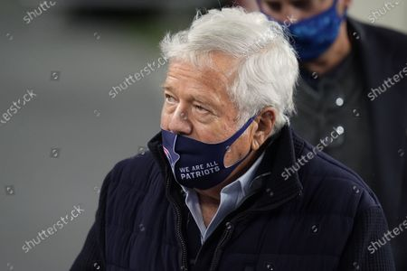 New England Patriots owner Robert Kraft wears a protective mask during the coronavirus pandemic as he team warms up before an NFL football game against the Baltimore Ravens, in Foxborough, Mass