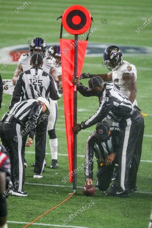 Referee Shawn Hochuli (83) checks the spot of the ball, held by field judge Tom Hill (97), against the chain marker held by umpire Ramon George (128) during the second half of an NFL football game between the Baltimore Ravens and New England Patriots, in Foxborough, Mass