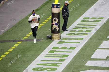Stock Photo of Baltimore Ravens quarterback Robert Griffin III (3) runs past the Salute to Service painted on the end line prior to an NFL football game against the New England Patriots, in Foxborough, Mass