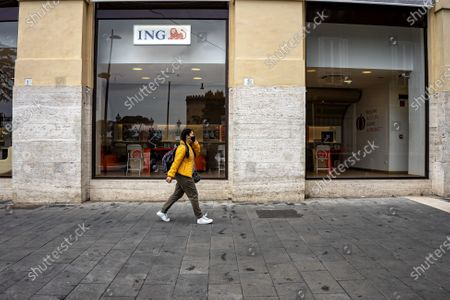 Stock Image of ITALY - NAPLES 11/15/2020 CAMPANIA: Red zone, day 1: few passersby. A dive back in time what Napoli does on Sunday 15 November. It seems to be back in March, when the whole of Italy was forced to the loclkdown by the pandemic by Covid-19. Semi-deserted streets. A few passers-by and a few bicycles, even fewer people in the historic center. In via Toledo, some citizens stroll among the closed shutters of bars and shops. Massive presence of police and army to control the territory. A girl walking through the streets of Naples.