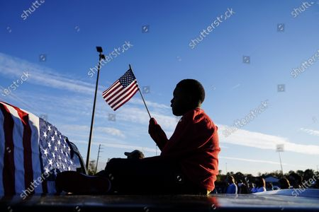 Stock Picture of Xavier Watts, 9, waves an American flag during a camping rally for Georgia Democratic U.S. Senate candidates Jon Ossoff and Raphael Warnock, in Marietta, Ga