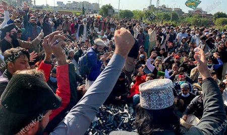 Supporters of 'Tehreek-e-Labaik Pakistan, a religious political party, chant slogans while they block a main highway during an anti-France rally over the remarks of French President Emmanuel Macron, in Islamabad, Pakistan, . The supporters are protesting the French leader over his recent statements and the republishing in France of caricatures of the Muslim Prophet Muhammad they deem blasphemous