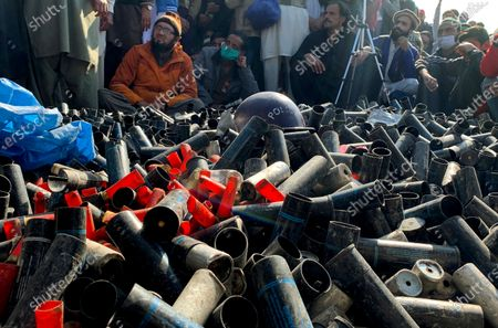Supporters of 'Tehreek-e-Labaik Pakistan, a religious political party, sit beside empty tear gas shells fired by police to stop them enter in to capital during an anti-France rally over the remarks of French President Emmanuel Macron, in Islamabad, Pakistan, . The supporters are protesting the French leader over his recent statements and the republishing in France of caricatures of the Muslim Prophet Muhammad they deem blasphemous