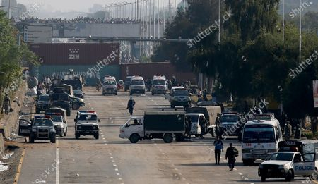 Security vehicles park near shipping containers placed by authorities on a highway to stop supporters of the 'Tehreek-e-Labaik Pakistan, a religious political party, entering into the capital during an anti-France rally in Islamabad, Pakistan, . The supporters are protesting the French President Emmanuel Macron over his recent statements and the republishing in France of caricatures of the Muslim Prophet Muhammad they deem blasphemous