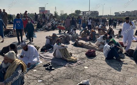 Stock Photo of Supporters of 'Tehreek-e-Labaik Pakistan, a religious political party, take a rest while blocking a main road during an anti-France rally in Islamabad, Pakistan, . The supporters are protesting the French President Emmanuel Macron over his recent statements and the republishing in France of caricatures of the Muslim Prophet Muhammad they deem blasphemous