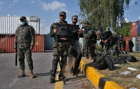 Paramilitary soldiers stand guard beside the shipping containers placed by authorities on a highway to stop supporters of 'Tehreek-e-Labaik Pakistan, a religious political party, entering into the capital during an anti-France rally in Islamabad, Pakistan, . The supporters are protesting the French President Emmanuel Macron over his recent statements and the republishing in France of caricatures of the Muslim Prophet Muhammad they deem blasphemous