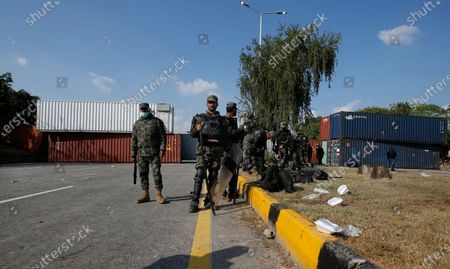 Paramilitary soldiers stand guard beside shipping containers placed by authorities on a highway to stop supporters of 'Tehreek-e-Labaik Pakistan, a religious political party, entering into the capital during an anti-France rally in Islamabad, Pakistan, . The supporters are protesting the French President Emmanuel Macron over his recent statements and the republishing in France of caricatures of the Muslim Prophet Muhammad they deem blasphemous