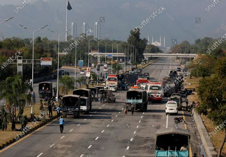 Security vehicles park along a highway blocked by authorities to stop supporters of 'Tehreek-e-Labaik Pakistan, a religious political party, from entering into the capital during an anti-France rally in Islamabad, Pakistan, . The supporters are protesting the French President Emmanuel Macron over his recent statements and the republishing in France of caricatures of the Muslim Prophet Muhammad they deem blasphemous