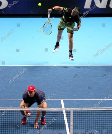 John Peers of Australia, front, and Michael Venus of New Zealand, back, serves to Marcel Granollers of Spain and Horacio Zeballos of Argentina during their doubles match at the ATP World Finals tennis match at the O2 arena in London