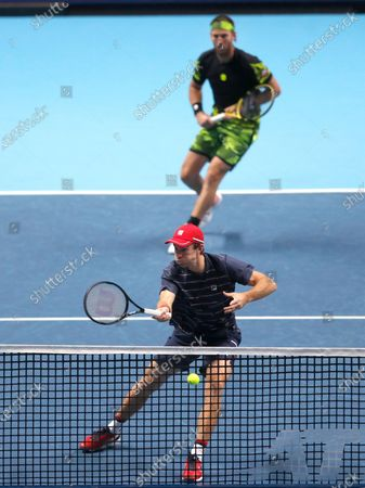 John Peers of Australia, front, and Michael Venus of New Zealand, back, play a return to Marcel Granollers of Spain and Horacio Zeballos of Argentina during their doubles match at the ATP World Finals tennis match at the O2 arena in London