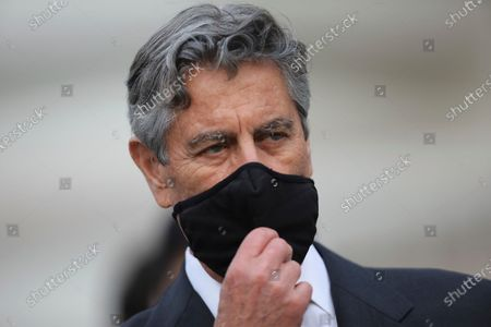 Peru's new interim President Francisco Sagasti takes off his mask after he was designated by Congress to lead the nation, in Lima, Peru, . Lawmakers chose Sagasti to become the nation's third president in the span of a week after they ousted Martin Vizcarra and the following protests forced his successor Manuel Merino to resign