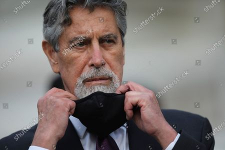 Peru's new interim President Francisco Sagasti takes off his mask after he was designated by Congress to lead the nation, in Lima, Peru, . Congress chose Sagasti to become the nation's third president in the span of a week after Congress ousted Martin Vizcarra and the following protests forced his successor Manuel Merino to resign