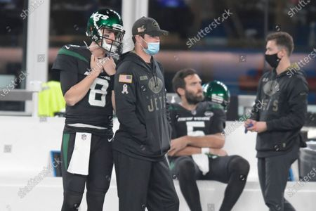 New York Jets quarterback Sam Darnold, center left, looks on from the sidelines during the first half of an NFL football game against the New England Patriots, in East Rutherford, N.J. Jets quarterback Sam Darnold will be sidelined for a second straight game as he recovers from an injured right shoulder. Coach Adam Gase said Monday that Joe Flacco will start in Darnold's place when the winless Jets take on the Chargers in Los Angeles on Sunday
