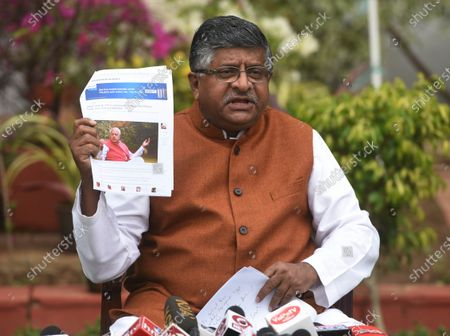 Union Minister Ravi Shankar Prasad holds up news clippings of statements by National Conference leader Farooq Abdullah, during a press conference at his residence on November 16, 2020 in New Delhi, India.