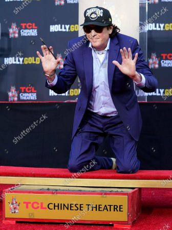 Actor Michael Madsen holds up his hands after writing his name in cement during a ceremony for him at the TCL Chinese Theatre, in Los Angeles