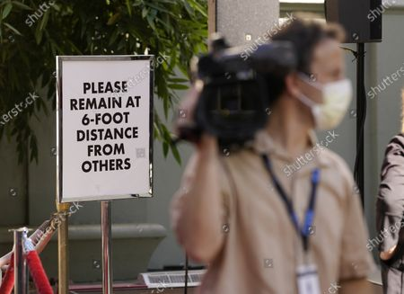 Sign advises spectators and media members to keep distance before a hand and footprint ceremony for actor Michael Madsen at the TCL Chinese Theatre, in Los Angeles