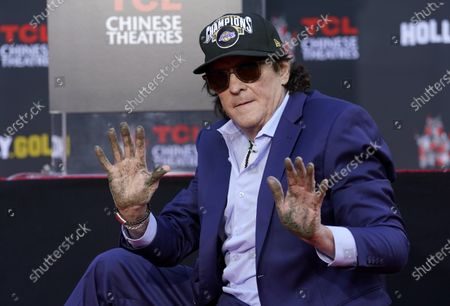 Actor Michael Madsen holds up his hands after putting them in cement during a ceremony for him at the TCL Chinese Theatre, in Los Angeles