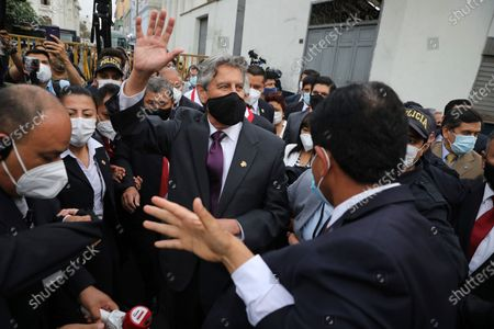 Peru's new interim President Francisco Sagasti waves to the crowd after he was designated by Congress to lead the nation, in Lima, Peru, . Congress chose Sagasti to become the nation's third president in the span of a week after Congress ousted Martin Vizcarra and the following protests forced his successor Manuel Merino to resign