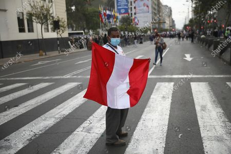 Man holds a Peruvian flag at a street crossing after Peru's new interim President Francisco Sagasti was designated by Congress to lead the nation, in Lima, Peru, . Lawmakers chose Sagasti to become the nation's third president in the span of a week after they ousted Martin Vizcarra and the following protests forced his successor Manuel Merino to resign