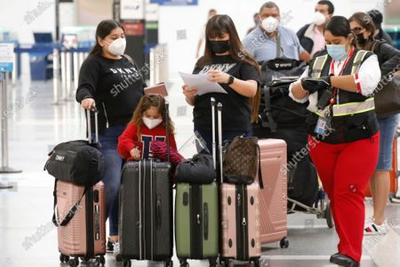 Cindy Perla, middle, is flying with her niece 4-year-old Ashley Grace to El Salvador on Monday November 16, 2020 as weekly coronavirus cases have doubled in just the last month around the state, and Los Angeles County had the grim distinction of recording more than 6,800 cases this weekend alone, an alarming spike that has officials talking about more restrictions. California officials are urging those who do head out of state to self-quarantine for 14 days when they return. LAX Los Angeles Airport on Monday, Nov. 16, 2020 in Los Angeles, CA. (Al Seib / Los Angeles Times