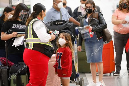 Stock Image of A Passenger Service Representative for Avianca Airlines in the Tom Bradley International Terminal at LAX takes the temperature of 4-year-old Ashley Grace who is flying with her aunt Cindy Perla, left, to El Salvador on Monday November 16, 2020 as weekly coronavirus cases have doubled in just the last month around the state, and Los Angeles County had the grim distinction of recording more than 6,800 cases this weekend alone, an alarming spike that has officials talking about more restrictions. California officials are urging those who do head out of state to self-quarantine for 14 days when they return. LAX Los Angeles Airport on Monday, Nov. 16, 2020 in Los Angeles, CA. (Al Seib / Los Angeles Times