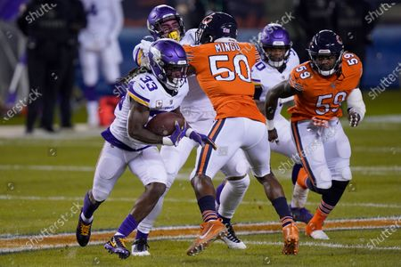 Minnesota Vikings running back Dalvin Cook (33) runs with the ball as Chicago Bears linebacker Barkevious Mingo (50) and linebacker Danny Trevathan (59) defend during the first half of an NFL football game, in Chicago