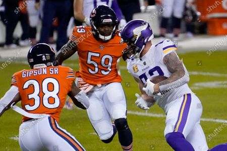 Minnesota Vikings tight end Kyle Rudolph, right, runs with the ball before fumbling for a turnover as Chicago Bears linebacker Danny Trevathan (59) and safety Tashaun Gipson Sr. (38) defend during the first half of an NFL football game, in Chicago. The Bears recovered the fumble