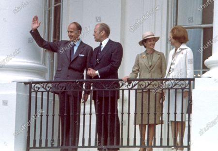 President Valéry Giscard d'Estaing of France, left, waves to the crowd as United States President Gerald R. Ford, left center, looks on as he is welcomed to the White House in Washington, DC for a State Visit. Anne-Aymone Giscard d'Estaing, right center, and first lady Betty Ford, right, are pictured with their husbands.