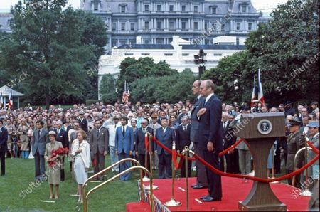 United States President Gerald R. Ford, right, welcomes President Valéry Giscard d'Estaing of France, left, to the White House in Washington, DC for a State Visit. At left are Anne-Aymone Giscard d'Estaing and first lady Betty Ford.