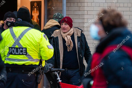 Stock Image of Woody Harrelson after shooting wraps for the day, chatting with local police and crew. The film is being shot in the midst of the coronavirus pandemic, with safety protocols and testing in place.