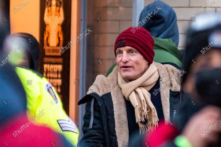 Stock Photo of Woody Harrelson after shooting wraps for the day, chatting with local police and crew. The film is being shot in the midst of the coronavirus pandemic, with safety protocols and testing in place.