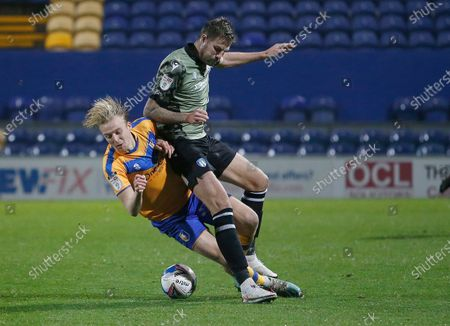 Mansfield Town's George Lapslie battles with Colchester United's Harry Pell
