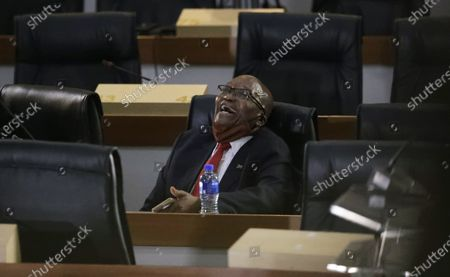 Former South African President Jacob Zuma, laughs as he waits for the state capture hearings to get underway in Johannesburg, . Zuma is appearing before a state commission investigating serious allegations of corruption during his tenure as head of state between 2009 and 2018