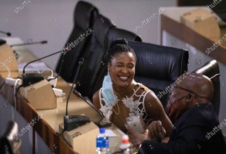 Former South African President Jacob Zuma, right, reacts with his daughter Duduzile Zuma, as he waits for the state capture hearings to get underway in Johannesburg, . Zuma is appearing before a state commission investigating serious allegations of corruption during his tenure as head of state between 2009 and 2018