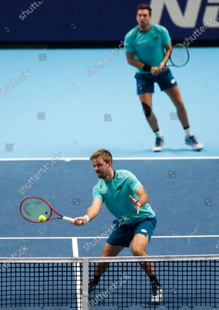 Kevin Krawietz of Germany, front, and Andreas Mies of Germany, behind, play a return to Lukasz Kubot of Poland and Marcelo Melo of Brazil during their doubles tennis match at the ATP World Finals tennis tournament at the O2 arena in London