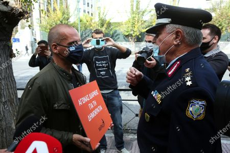 Greek Secretary-General of MeRA25, left-wing political party, Yanis Varoufakis (L) holds a placard while standing in front of a policeman who informs him that gatherings are banned at the Polytechnic school, during the anniversary commemorating the victims of the 1973 uprising against the military junta, in Athens, Greece, 17 November 2020. The entrance to the Polytechnic University remains closed, during the second lockdown of the country, to stem the spread of the coronavirus pandemic. A four-day order banning gathering of over four people has been imposed throughout Greece. The ban, effective November 15 to 18, comes ahead of commemorations for November 17, the anniversary of the Polytechnic student uprising against the junta in 1973, and an annual march to the US embassy.