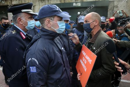 Stock Picture of Greek Secretary-General of MeRA25, left-wing political party, Yanis Varoufakis (R) holds a placard while standing in front of a policeman who informs him that gatherings are banned for the anniversary commemorating the victims of the 1973 uprising against the military junta in the Polytechnic School, in Athens, Greece, 17 November 2020. The entrance to the Polytechnic University remains closed, during the second lockdown of the country, to stem the spread of the coronavirus pandemic. A four-day order banning gathering of over four people has been imposed throughout Greece. The ban, effective November 15 to 18, comes ahead of commemorations for November 17, the anniversary of the Polytechnic student uprising against the junta in 1973, and an annual march to the US embassy.