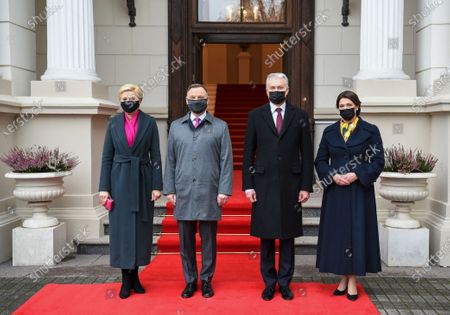 In this handout photo provided by the Lithuanian President's Office, Lithuania's President Gitanas Nauseda, second right, his wife Diana Nausediene, right, Poland's President Andrzej Duda, second left, and his wife Agata Kornhauser-Duda, left, pose for photographers prior to their meeting at the Presidential palace in Vilnius, Lithuania