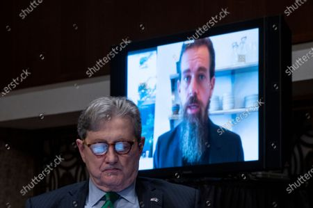 """Jack Dorsey, Chief Executive Officer of Twitter, testifies remotely as United States Senator John Neely Kennedy (Republican of Louisiana), looks at his iPad during the Senate Judiciary Committee hearing on """"Breaking the News: Censorship, Suppression, and the 2020 Election""""."""