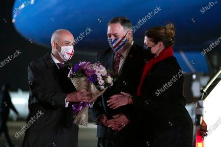 Georgian Foreign Minister David Zalkaliani, left, gives flowers to Susan Pompeo as she and her husband, Secretary of State Mike Pompeo, arrive at Tbilisi International Airport in Tbilisi, Georgia