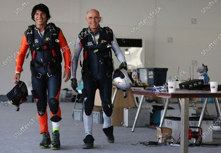"""Former Swiss pilot Yves Rossy, known as a """"jetman,"""" right, and his protege Vince Reffet, prepare for a fly in Dubai, United Arab Emirates. Reffet, one of Dubai's """"jetmen,"""" whose flights over the world's tallest building and alongside a jumbo jet with engines strapped to his back wowed watchers online, died, while training in the deserts of the Arabian sheikhdom, his organization said"""