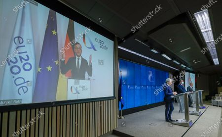 Stock Photo of German Minister of State for European Affairs Michael Roth (on screen via video) and  European Commissioner for Justice Didier Reynders (L) with EU Commission Vice President Maros Sefcovic (R) during a news conference at the end of a Informal Video conference of European Affairs Ministers in Brussels, Belgium, 17 November 2020. European ministers' discussion mainly focused on Rule of Law and Multi annual framework (MFF), after Poland and Hungary announce a day earlier they will veto the European budget.